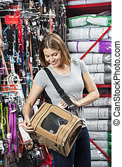 Woman Examining Pet Carrier In Store - Smiling mid adult...