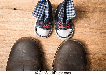 Daddy's boots and baby's sneakers, on wood background,...