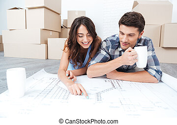 Happy couple looking at construction house plan