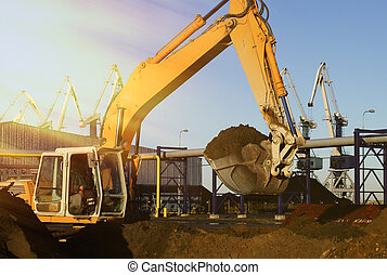 Hydraulic excavator at work. Shovel bucket and cranes against blue sky