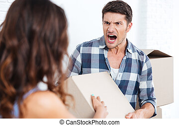 Young married couple arguing during relocation in new house
