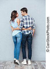 Young happy couple standing backwards over gray background -...