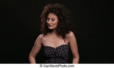 Young brunette with long brown curly hair dancing on a black...