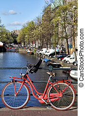 Herengracht in Amsterdam - Red bicycle on a bridge over the...