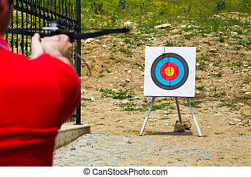 Man taking aim with a crossbow at a target - Man taking aim...