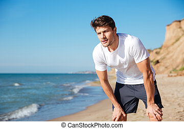 Man in white t-shirt and shorts standing on beach - Portrait...
