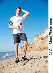 Attractive young sportsman with bottle of water on the beach...