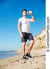 Sportsman standing and drinking water on the beach -...