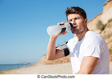 Sportsman sitting and drinking water on the beach - Serious...
