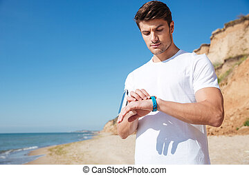 Sportsman standing and using smart watch on the beach -...
