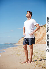 Relaxed man standing barefoot on the beach - Attractive...