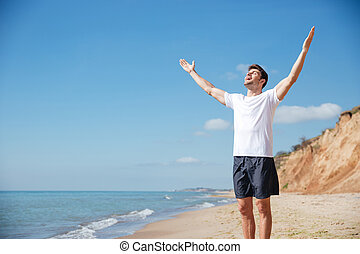 Cheerful man with outstretched arms standing on the beach