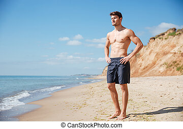 Relaxed young man standing on the beach - Handsome relaxed...