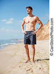 Confident athletic young man standing on the beach -...