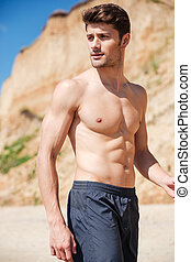 Handsome young man in black shorts on the beach - Portrait...