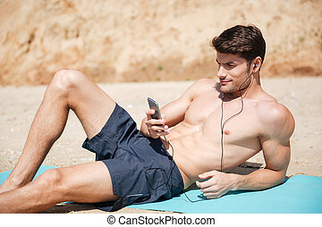 Man listening to music from mobile phone on the beach -...