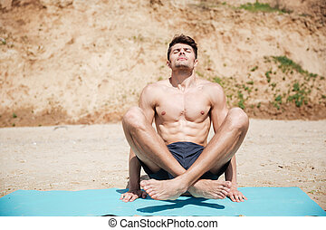 Man practicing yoga on the beach - Relaxed handsome young...