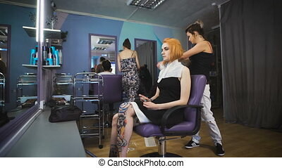 Beautiful girl in the client's chair beauty salon. Her...