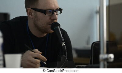 Bearded man in glasses speaks into the microphone. He is...