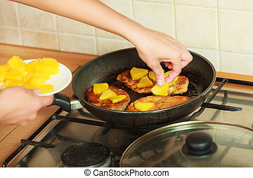 Human frying chicken cutlet with pineapples - Human frying...