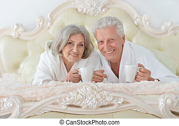 Senior couple in bed with tea - happy Senior couple reading...