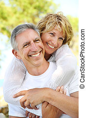 Mature couple smiling and embracing Focus on the man