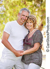 Mature couple smiling and embracing Focus on the woman