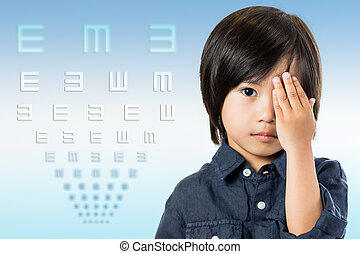 Asian boy testing vision with chart. - Close up conceptual...