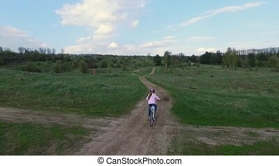 little girl rides bicycle on country road