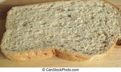 Close up video: spreading creamy butter on a piece of bread...