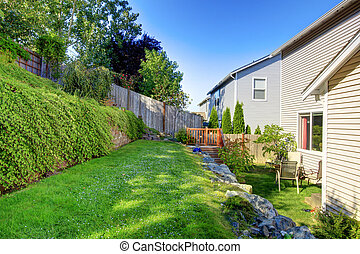 Small green fenced back yard with nice garden.