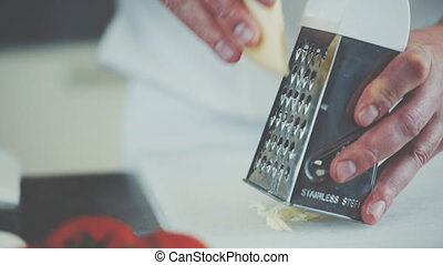 The cook rubs cheese on a grater