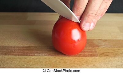 Man splitting ripe red tomato with white knife clip