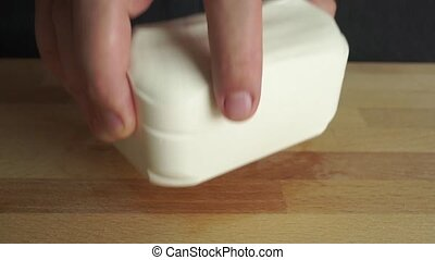 Splitting big piece of feta cheese with white knife clip