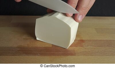 Man cutting off a piece of white soft feta cheese