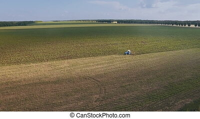 flying over a tractor plowing a field