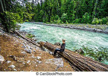 Woman sitting on a Log at the Lillooet River in Nairn Falls...