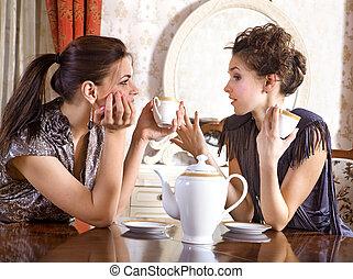 Two pretty girl-friends drink tea - Two pretty girl-friends...