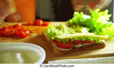 Woman making sandwich with salad leaf, spread, cherry tomatoes and cheese
