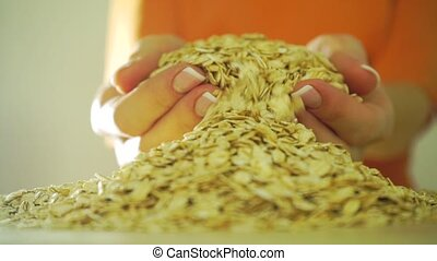 Girl in orange clothes scooping rolled oats with her hands, slow motion video