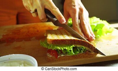Girl cutting sandwich with salad leaf, spread, cherry tomatoes and cheese