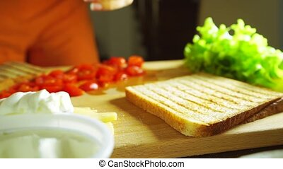 Making a sandwich: spreading soft cheese on a toasted bread