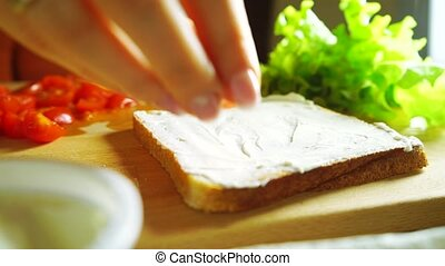 Placing cherry tomato pieces on a sandwich, close up video -...