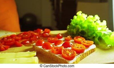 Placing leaf of fresh green salad on a sandwich