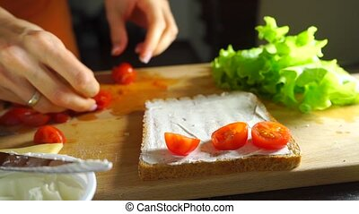 Young woman making sandwich with salad leaf, spread, cherry tomatoes and cheese