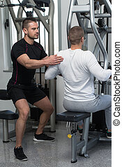 Personal Trainer Helping Client In Gym