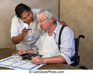 Feeding elderly man - Nurse in old people's home trying to...