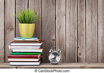 Wooden shelf with books and supplies in front of wooden wall...