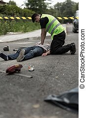 Policeman resuscitating injured man - Photo of policeman...