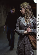 Hearing the footsteps - Shot of a young woman walking down...